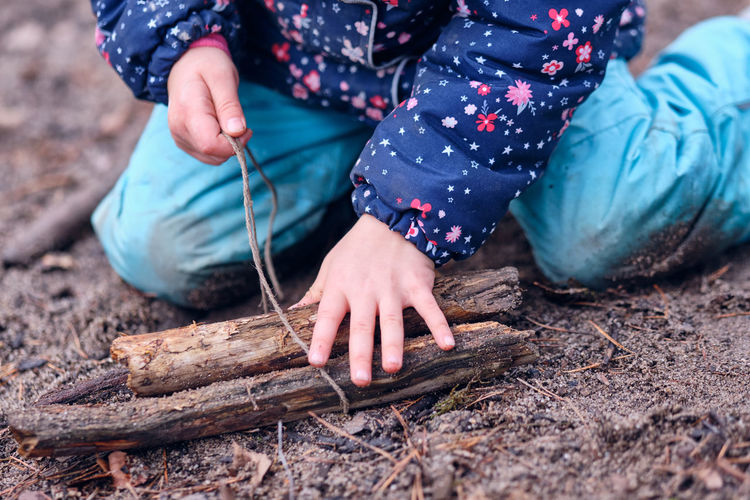 Midsection of girl holding sticks while sitting outdoors