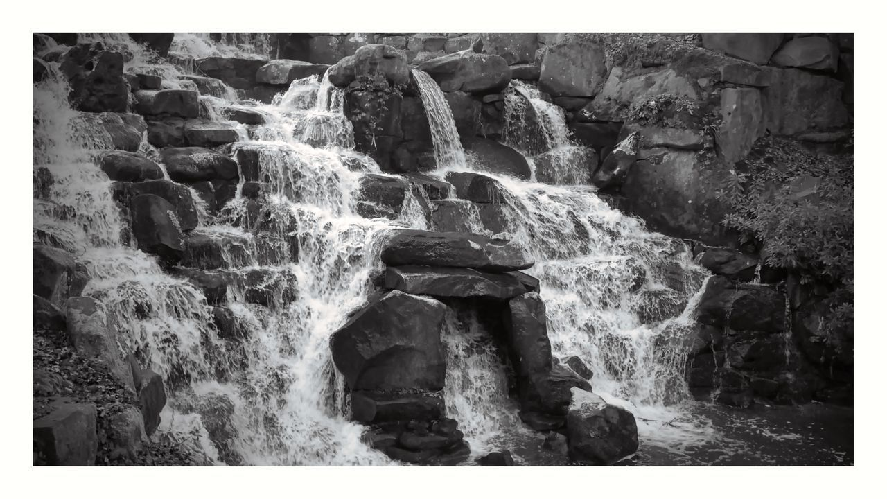 WATER FLOWING THROUGH ROCKS AGAINST WATERFALL