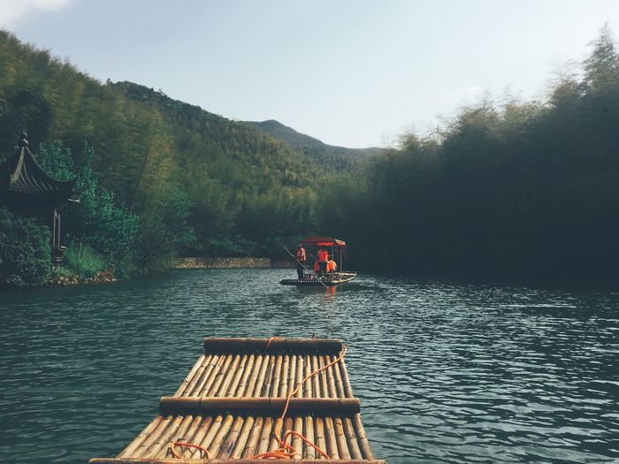 Wooden raft on river with people in boat against mountain