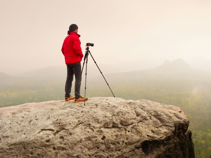 Photographer think about picture on peak in mountains. photograph above valley hidden in heavy mist.