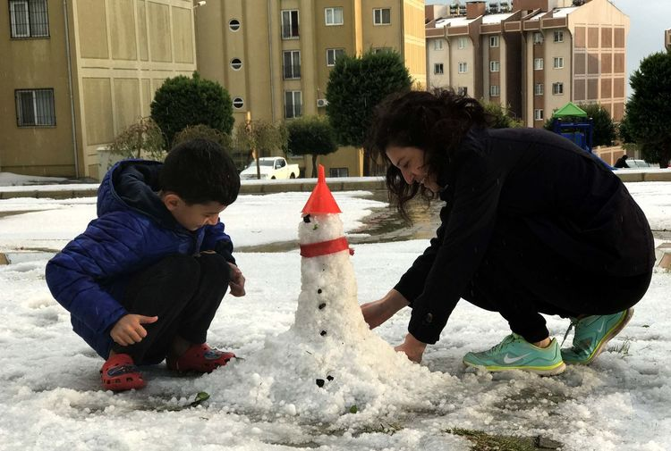 Mother and son playing in snow during winter