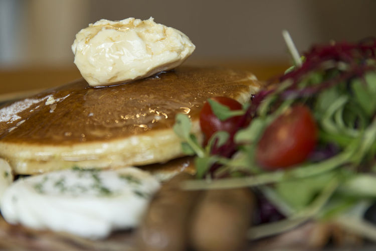 Close-up of pancakes with salad and poached egg in plate on table