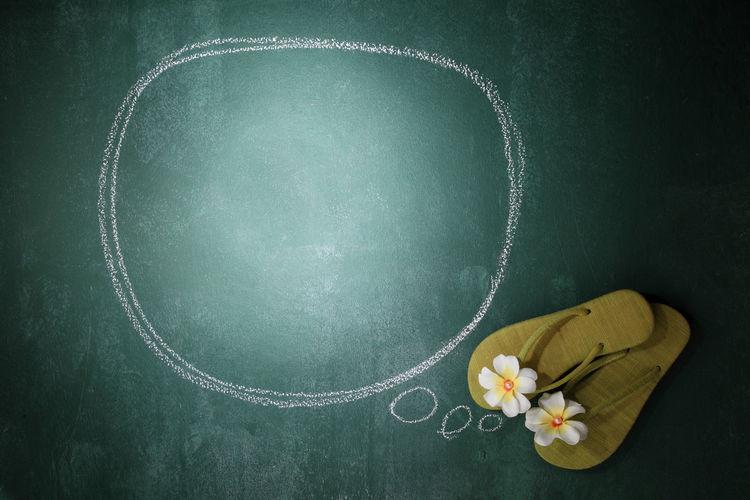 Flip-Flop With Flower By Speech Bubble On Blackboard