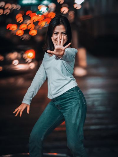 Portrait of young woman gesturing while standing outdoors