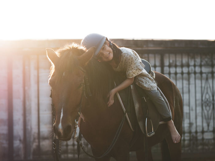 Asian school kid girl with horse ,riding or practicing horse ridding at horse ranch.
