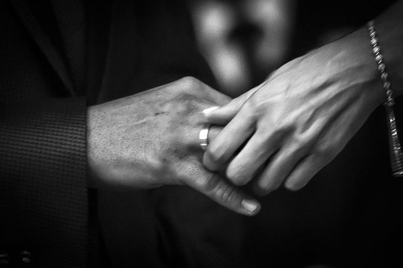 Cropped hand of bride putting ring in groom finger