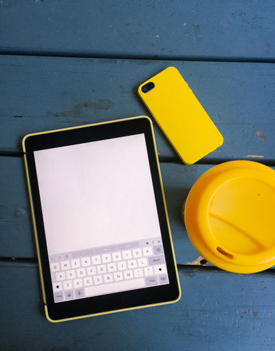 Yellow tablet computer, mobile smart phone and travel mug together on rustic blue table. Background Blank Blue Blue Color Close-up Communication Control Copyspace Day Devices Information Information Sign Mobile Morning No People Smart Phone Smartphone Still Life Tablet Text Travel Mug Work Working Yellow