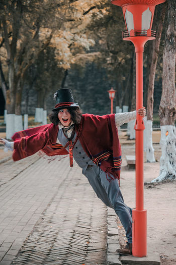 Portrait of man cosplaying mad hatter spinning around lamp post