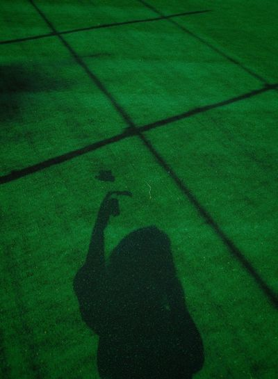 Shadow of person on green grass