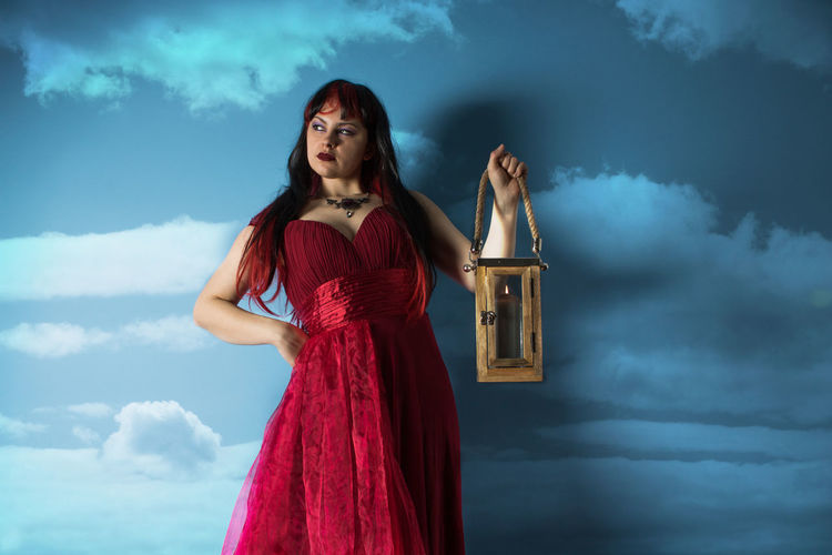 Beautiful woman holding lantern standing against blue background