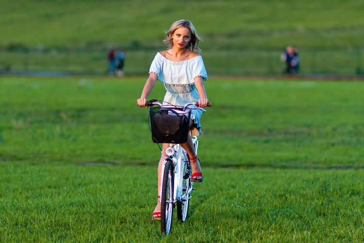 Soft focus photo. A young, beautiful blond woman with a white bike in a green meadow. One Person Day Blonde Young Adult Woman Women Girl Female Beauty Fashion Green Background Eyes Portrait Summer Face People Nature Model Hair Spring Cute Skin Smilling Field Outdoors person Caucasian White Attractive Pretty Smile Season  Elégance Luxury Glamour Outside Gorgeous Hairstyle Shoulders Design Copy Space Copyspace Modern Bike Bicycle Cicling Basket Biking Grass Land Casual Clothing Real People Plant Green Color Lifestyles Transportation Leisure Activity Full Length Focus On Foreground Front View Land Vehicle Riding