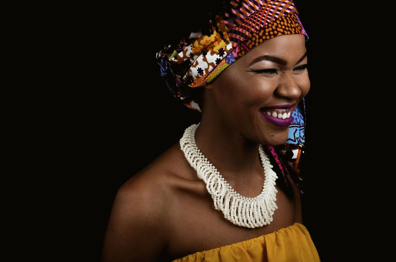 Black Woman African Woman  Headwrap  Happy African Fabric Portrait Makeup Eyes Lips Lipstick Eyelash Eyeliner African Accessories Smiling Teeth Pearl Jewelry Fashion Studio Shot Black Background One Person Indoors  Front View Young Adult Women Young Women Lifestyles Beautiful Woman Happiness Headshot Emotion Looking Away Cut Out Looking Copy Space Beauty