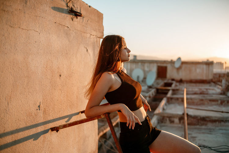 Young woman on terrace during sunset