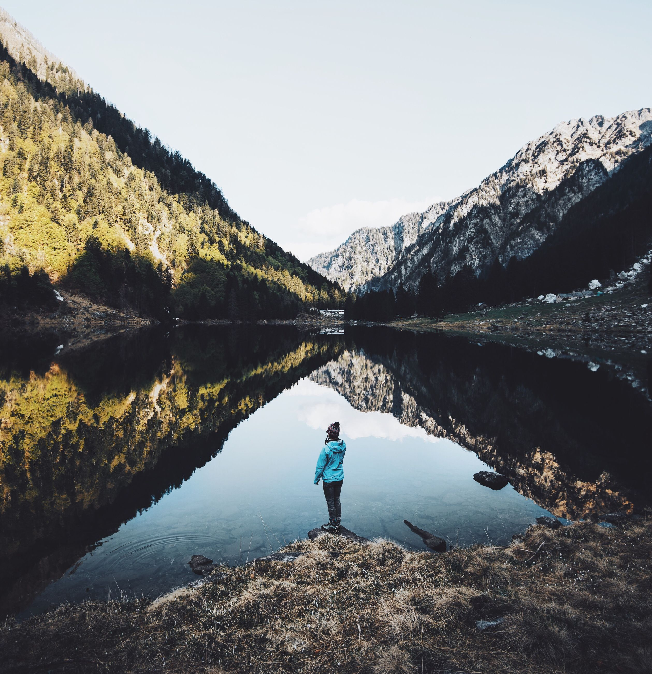 reflection, water, lake, real people, outdoors, nature, leisure activity, one person, beauty in nature, tranquility, standing, tranquil scene, day, scenics, growth, sky, full length, mountain, tree