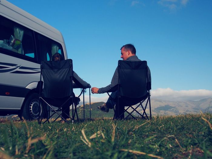 Friends sitting on chairs by vehicle on field against blue sky