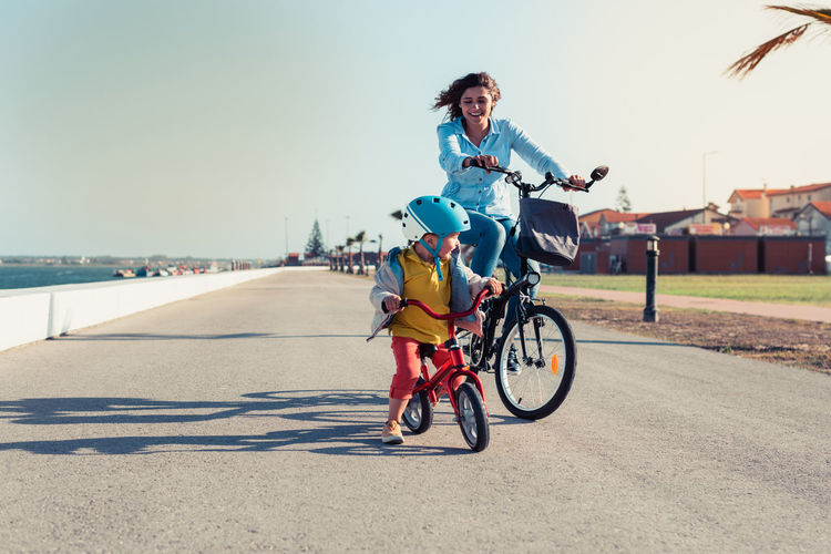 Woman and son riding bicycle on road in city