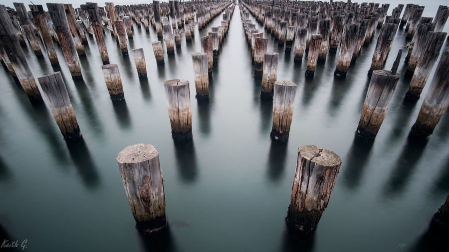 High angle view of wooden posts in river