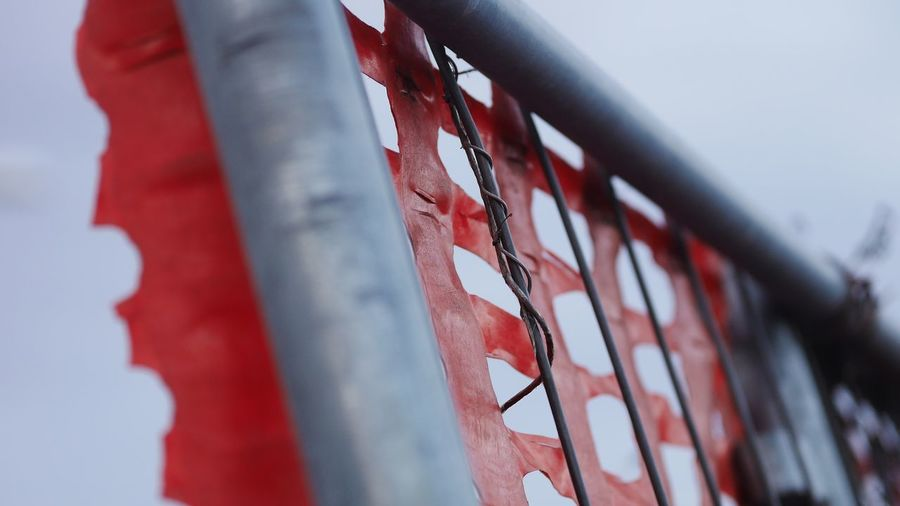 EyeEm Selects Red No People Day Nature Close-up Hanging Outdoors Built Structure Sky Architecture Selective Focus Metal Low Angle View Wall - Building Feature Flag Focus On Foreground Pattern Fence Textile
