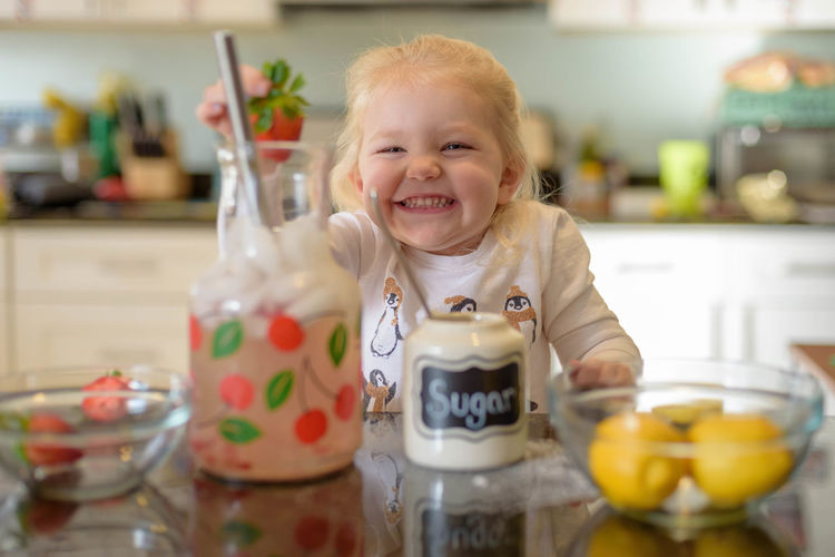 Portrait of cute girl holding strawberry in kitchen at home
