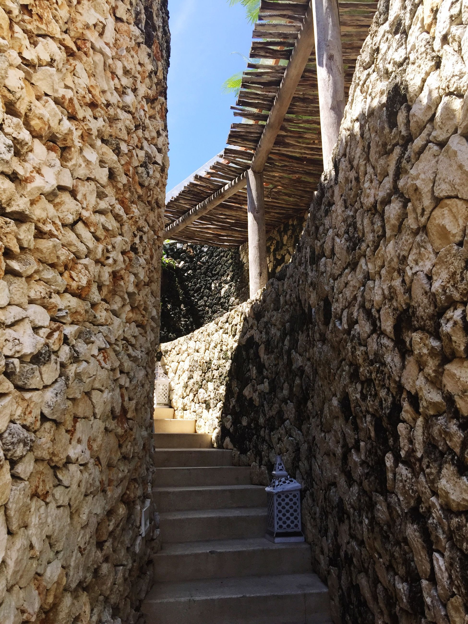 steps, steps and staircases, built structure, architecture, staircase, the way forward, stone wall, building exterior, low angle view, stairs, railing, stone material, sunlight, history, stone, rock - object, wall - building feature, diminishing perspective, day, leading