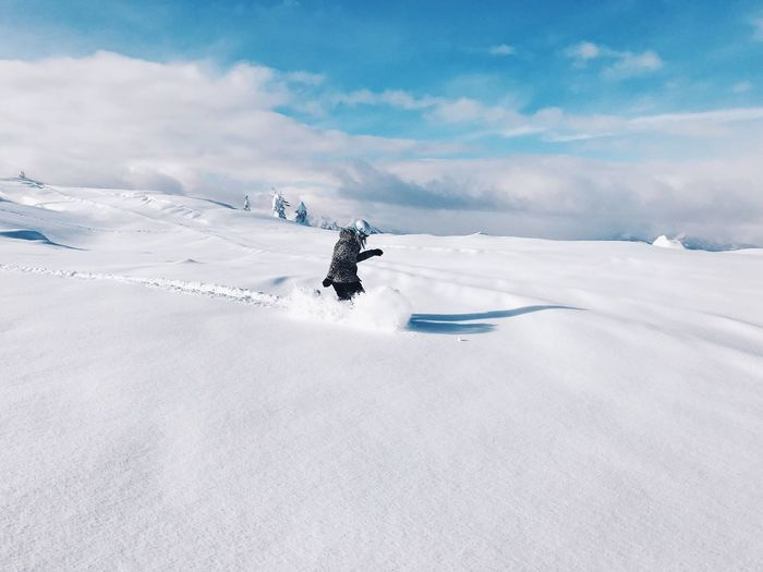 Person walking on snowcapped mountain against sky