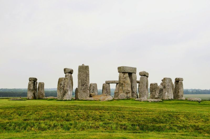 Stonehenge on grassy landscape against clear sky