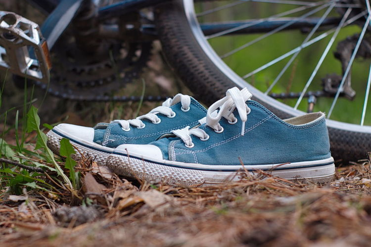 Close-up of canvas shoes against bicycles on field