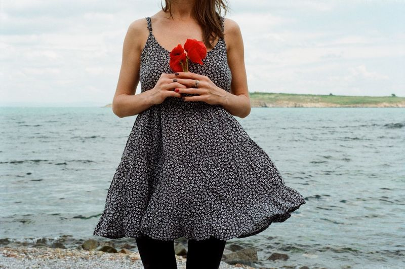 Midsection of woman holding red poppies while standing at beach