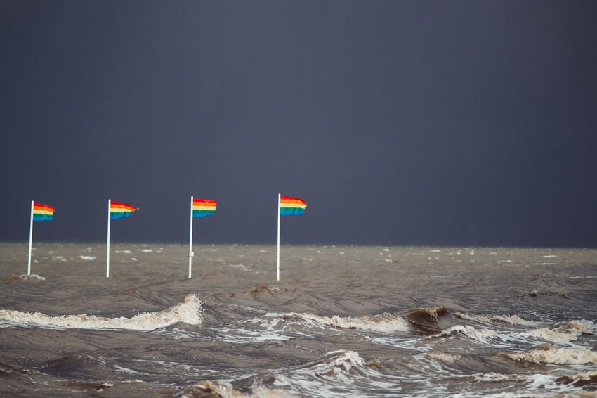 HEAVY WEATHER Storm Stormy Weather The Week On EyeEm Beach Beauty In Nature Day Flag Flags In The Wind  Gay Horizon Over Water Nature No People Outdoors Rainbow Flag Sand Scenics Sea Sea And Sky Sky Tranquil Scene Tranquility Water Be. Ready. This Is Queer