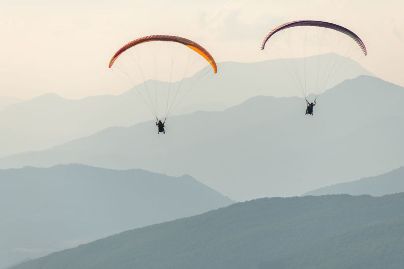 People paragliding against mountain range