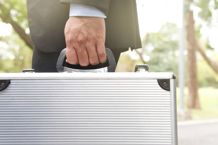 Midsection of businessman with suitcase walking outdoors