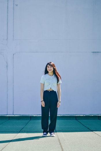 Full length of young woman smiling while standing against wall