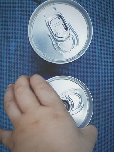 Cropped image of hand holding drink can