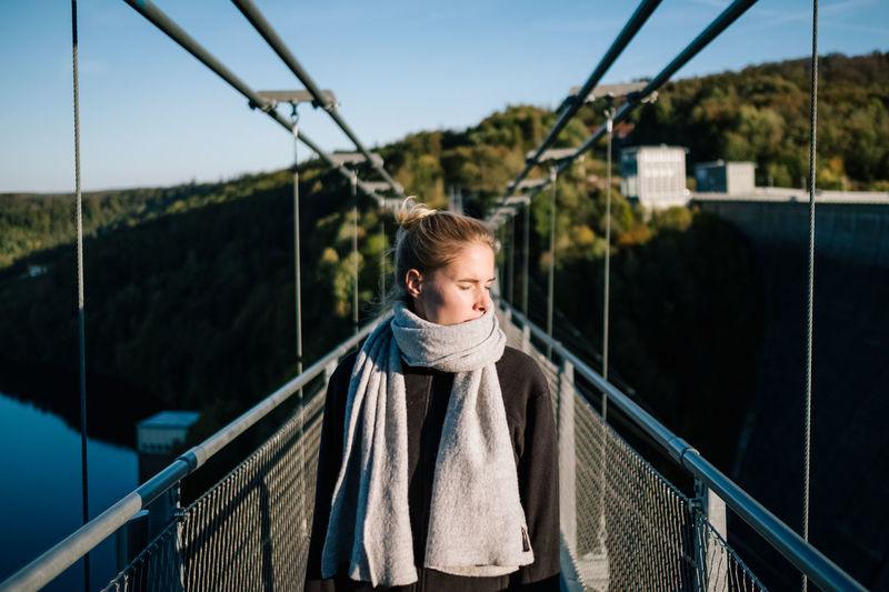 Woman on footbridge against sky