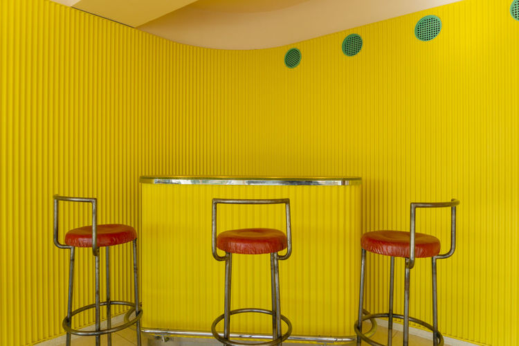 Empty chairs and table against yellow wall