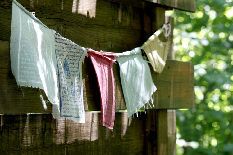 Prayer Flags Hanging On Clothesline By Wooden House