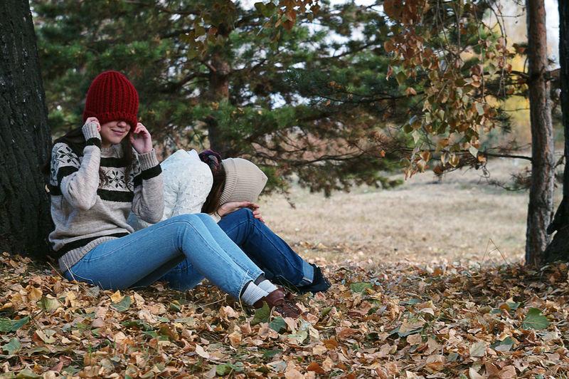 Full length of teenage girl sitting in park