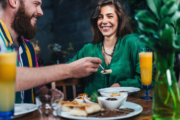 Smiling young couple enjoying lunch at table in restaurant
