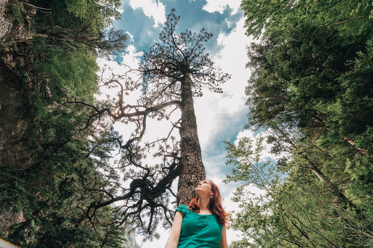 Woman against trees in forest
