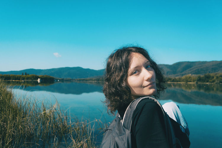 Girl sitting on the edge of banyoles lake on a sunny day with the landscape reflected in the water