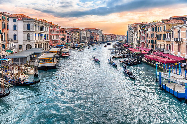 VENICE, ITALY - APRIL 29: Scenic view of the Grand Canal at sunset from the iconic Rialto Bridge, one of the major landmark in Venice, Italy, as seen on April 29, 2018 Architecture Building Building Exterior Built Structure Canal City Cloud - Sky Incidental People Mode Of Transportation Nature Nautical Vessel Outdoors Passenger Craft Residential District Sea Sky Sunset Transportation Water Waterfront