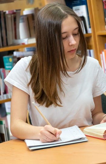 Teenage girl writing on book in library
