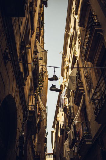 Low Angle View Of Shoes Hanging On Wire Amidst Buildings Against Sky