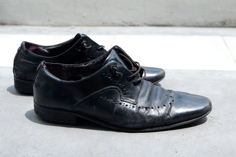 Close-up of black weathered shoes on floor