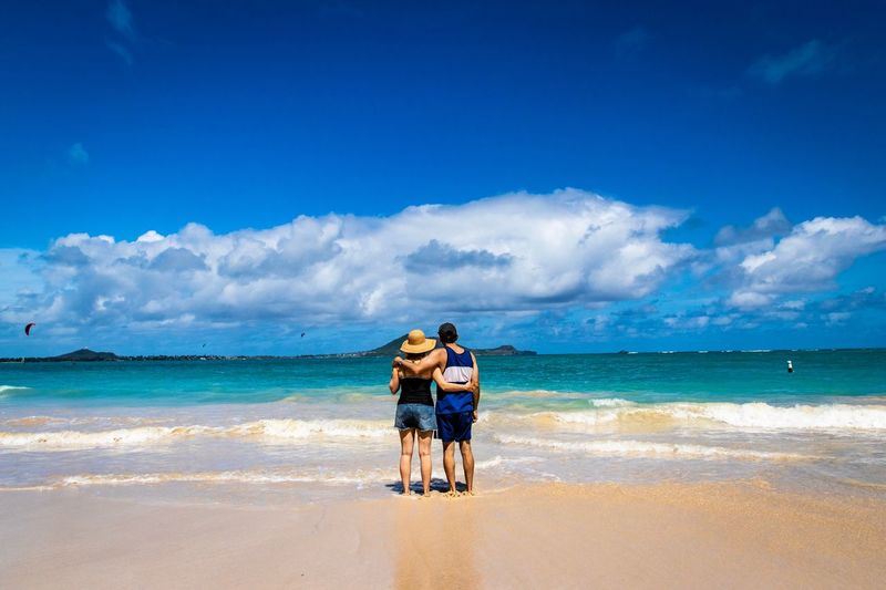 Full length of friends standing on shore at beach