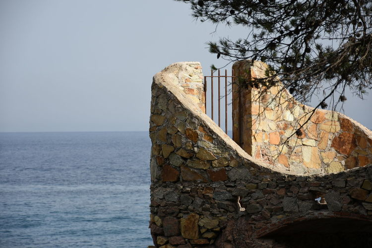 Stone wall by sea against clear sky