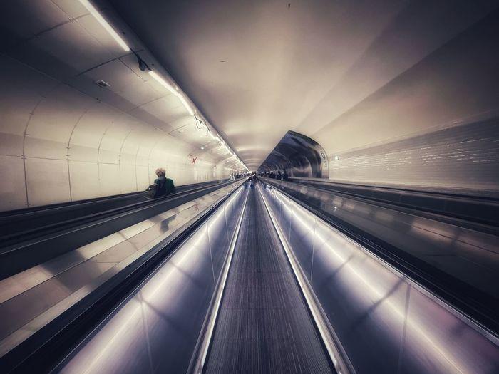 Light trails on escalator in illuminated underground walkway