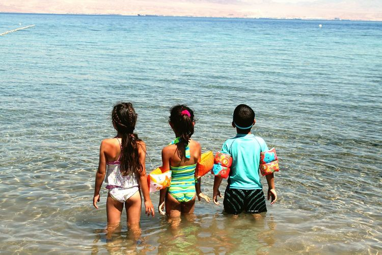 Rear View Of Boy And Girls Standing In Water On Sunny Day