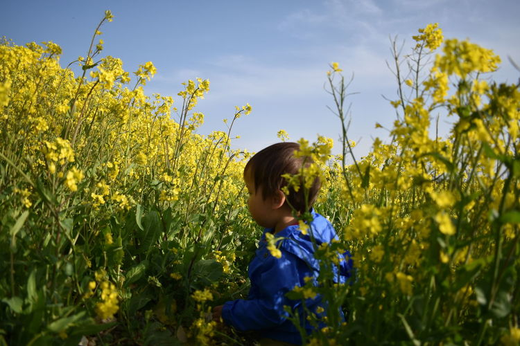 Baby with yellow flowers on field