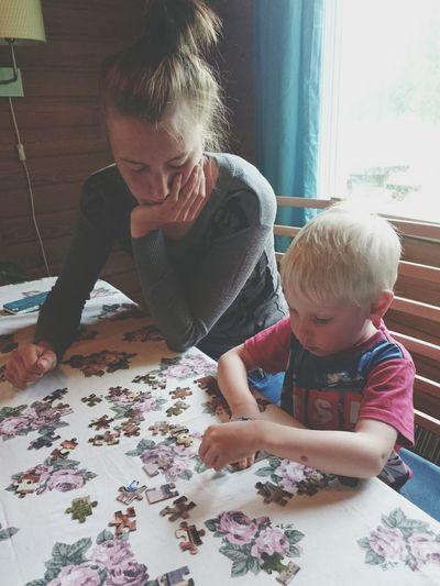 Boy Assembling Jigsaw Puzzle While Sitting By Mother At Table